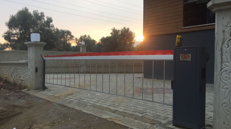 çit olarak da kullanılan otomatik kollu bariyer izinsiz olarak yapılacak araç giriş çıkışlarını engellemektedir
